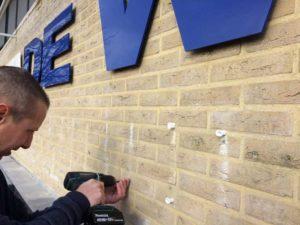 Frees- en laserletters monteren op bedrijfspand
